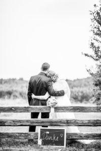Hochzeitspaar mit Blick auf See im Garten des Seehauses