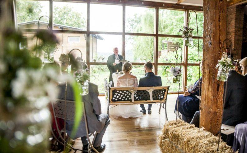 Hochzeitspaar während der Trauung in der Scheune mit Blick auf See