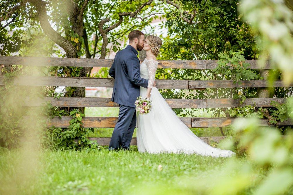 Hochzeitspaar im Garten vor Zaun