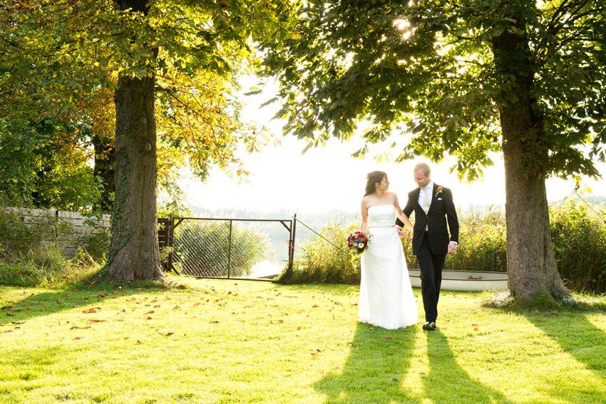 Hochzeitspaar im Garten unter den Bäumen am See